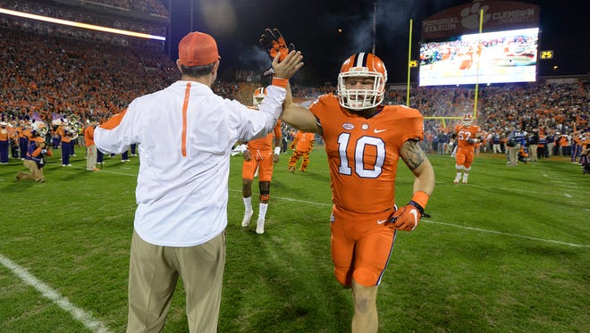 Clemson linebacker Ben Boulware (10) high-fives head coach Dabo Swinney during pregame before the Tigers' game against South Carolina on Saturday at Clemson's Memorial Stadium.