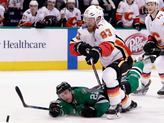 Dallas Stars defenseman Esa Lindell (23) of Finland dives to clear the puck away on an attack by Calgary Flames center Sam Bennett (93) during the second period of an NHL hockey game Tuesday, Feb. 27, 2018, in Dallas. (AP Photo/Tony Gutierrez)