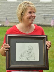 Traci Stacy holds a sketch of Mark Curry. Curry's friends and family gathered to remember fallen veterans Saturday.