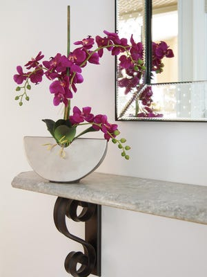 Orchids add natural contrast and softness to this foyer.