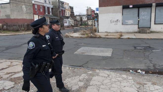 Two officers walk a beat in Camden last December. So far, the Camden County Police Department has only served the city, but Freeholder Director Lou Cappelli says two other towns are seriously considering signing on.
