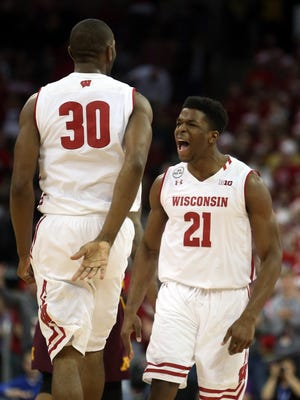 Badgers guard Khalil Iverson reacts to a dunk by forward Vitto Brown (30).