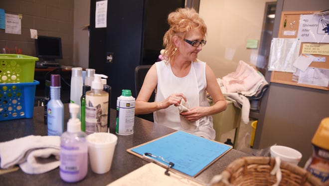 Client advocate Tammy Crow sorts through donated toiletries in the Men's Day Room Monday at Bishop Dudley Hospitality House. Crow said a lot of the time people will come in with bags are various items for donation.