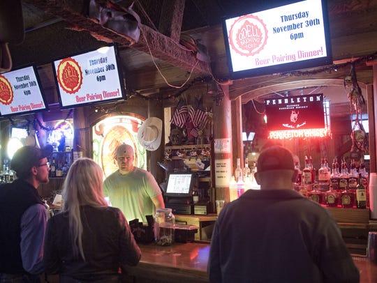 People mingle around the bar area at Sundance Steakhouse