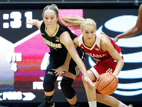 Tyra Buss of Indiana keeps the ball away from Karissa
