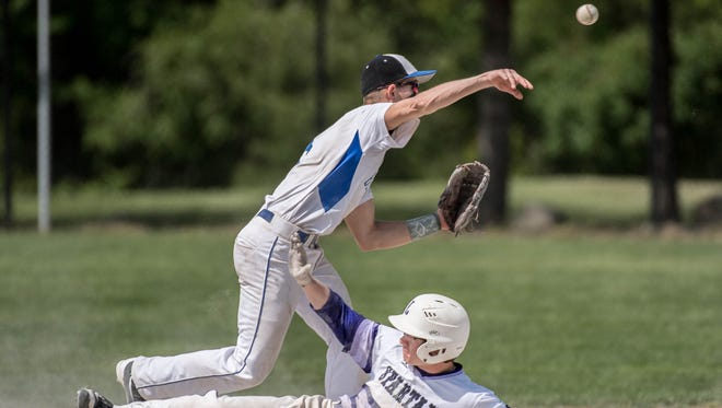 Harper Creek sophomore Dawson Bartlett throws to first as Lakeview junior Kevin Sprick slides into second.