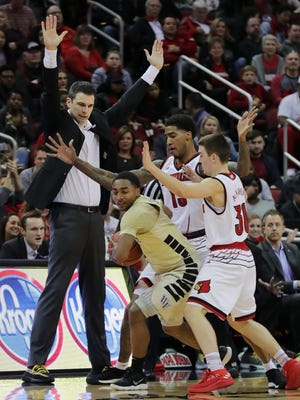 Louisville's Ray Spalding and Ryan McMahon trap Wake Forest's Brandon Childress with a little instruction from coach David Padgett.