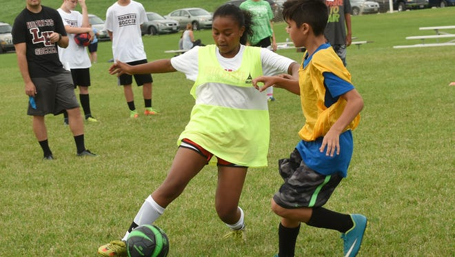 Ava Hill dodges Brian Fernandez during a 3-on-3 game at soccer camp on Tuesday, July 11, 2017 at Licking Heights High School.