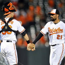 Aug 28, 2014; Baltimore, MD, USA; Baltimore Orioles catcher Caleb Joseph (36) and right fielder Nick Markakis (21) celebrate after a game against the Tampa Bay Rays at Oriole Park at Camden Yards. The Orioles defeated the Rays 5-4. Mandatory Credit: Joy R. Absalon-USA TODAY Sports