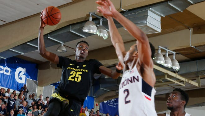 Oregon forward Chris Boucher goes up for a dunk against UConn guard Jalen Adams at the Lahaina Civic Center.