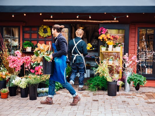 Florists carrying flowers outside shop