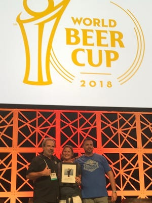 Rob Whyte, left, Jen Gratz-Whyte and TJ Jewell celebrate after Fort Myers Brewing Co. won silver Thursday at the 2018 World Beer Cup in Nashville.