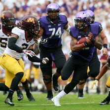 TCU Horned Frogs quarterback Trevone Boykin (2) runs with the ball in the first quarter while Minnesota Golden Gophers defensive back Derrick Wells (3) and defensive back Cedric Thompson (2) attempt the tackle at Amon G. Carter Stadium in Fort Worth on September 13, 2014.