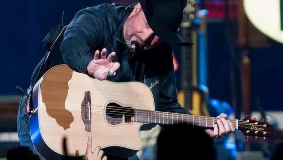 Garth Brooks hands a guitar pick down to a fan during
