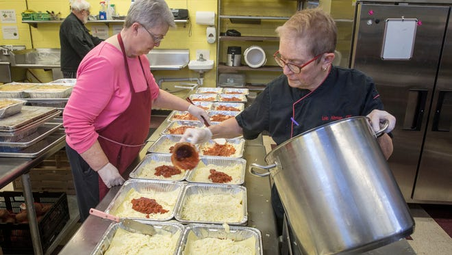 Lorretta Parsons, left, and Lois Altman, right, work on preparing 40 trays of lasagna for the dinner fundraiser on March 24. The fundraiser is critical for the organizations goal of feeding those in need.