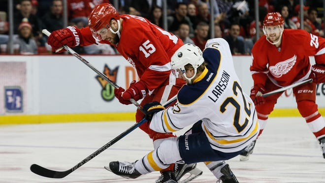 Detroit Red Wings forward Riley Sheahan, left, knocks the Buffalo Sabres'  Johan Larsson to the ice March 28, 2016.
