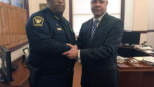 City Manager Harry Black shakes the hand of Eliot Isaac after naming Isaac interim Cincinnati police chief.