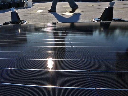 Workers work to install a second round of solar panels