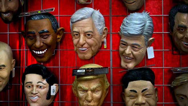 Masks representing the Mexico president-elect Andres Manuel Lopez Obrador, center, appear on display next to the masks of former U.S. President Barack Obama, Elvis Presley, U.S. President Donald Trump, and North Korean leader Kim Jong Un, at a market in Mexico City.