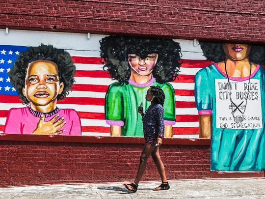 "Tanaya Nash, 10, passes the ""Rebirth of A Warrior"" mural painted by local artist Jamond Bullock during Stone Fest: A South Memphis Reunion at S. Wellington St. on Saturday, Aug. 26, 2017. Nash, of East Memphis, was visiting her great grandmother, Carolyn Townsend. ""It's very nice to see people and being together,"" Townsend said. ""Memphis music is always great."" The event, presented by the Stone Community Development Corporation, had games, food, entertainment, a bike and flat screen television giveaway and more."