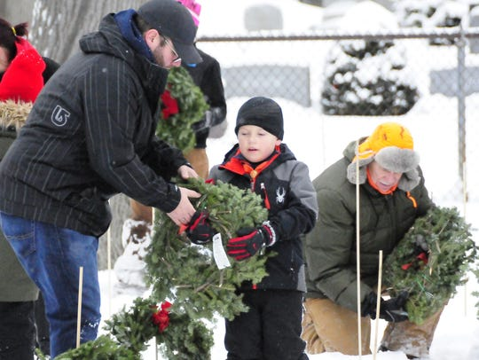 Families place wreaths during the Wreaths Across America