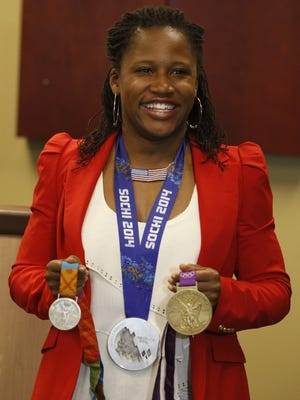 Olympic medalist Lauryn Williams poses with her three Olympic medals in Detroit on March 19, 2014.