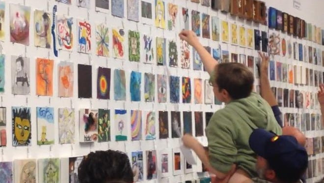 Patrons browse the artwork at the Rochester Contemporary Art Center's 6x6 opening party and sale on Saturday.