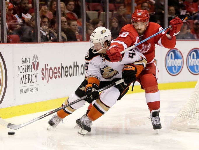 The Red Wings' Henrik Zetterberg, right, tries to pull