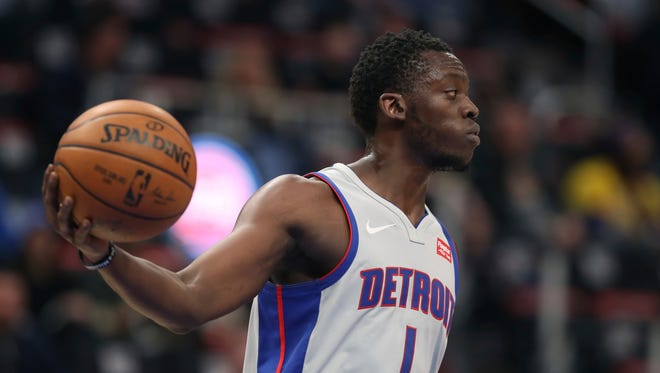 Pistons guard Reggie Jackson, right, reacts after scoring a 3-pointer against the Lakers on Monday night at Little Caesars Arena.