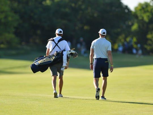 Michigan golfer Kyle Mueller, left, walks the course