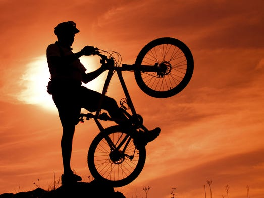 Young man with bike in sunset
