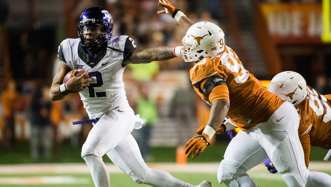 TCU's Trevone Boykin (2) holds off Texas' Paul Boyette Jr. (93) during the second half of a game on, Nov. 27 in Austin, Texas.