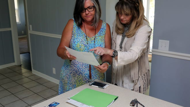 Sharon Kipp, left, with Benchmark Realty, reviews a listing with her client Lisa Powers after learning that an offer had just been accepted on the Donelson house they had gone to see Thursday September 22, 2016.
