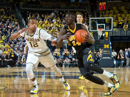 Michigan guard Muhammad-Ali Abdur-Rahkman (12) defends Iowa guard Peter Jok (14) in the first half of an NCAA college basketball game at Crisler Center in Ann Arbor, Mich., Saturday, March 5, 2016. (AP Photo/Tony Ding)