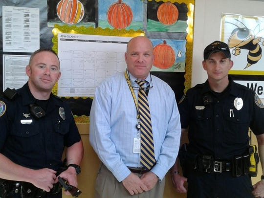 Springfield Middle School principal Grant Bell poses with two officers after lunch.