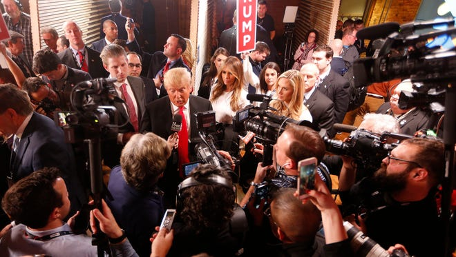 Republican presidential candidate, businessman Donald Trump with his wife Melania Trump at right,  speaks to the media in the spin room after the CBS News Republican presidential debate at the Peace Center, Saturday in Greenville, S.C.