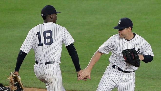 New York Yankees shortstop Didi Gregorius (18) and center fielder Jacoby Ellsbury celebrate after the Yankees defeated the Toronto Blue Jays 6-0 in a baseball game, Tuesday, May 24, 2016, in New York.