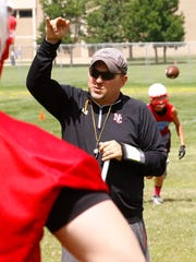 Head coach Paul Michlig, middle, works with football