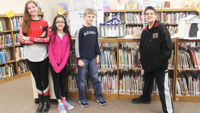 From left to right: Ava Lybarger, Anna Gayley, Tyler Randall and Paul McGraw show off class projects based on research about the Seven Wonders of the World.
