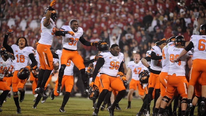 Oklahoma State Cowboys players celebrate a field goal against the Oklahoma Sooners in overtime. The Cowboys defeated the Sooners in overtime 38-35 at Gaylord Family - Oklahoma Memorial Stadium on Norman, Okla., on Dec. 6.