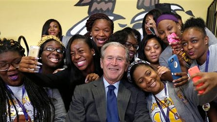 Former President George W. Bush poses for photos with students at Warren Easton Charter High School in New Orleans on Friday.