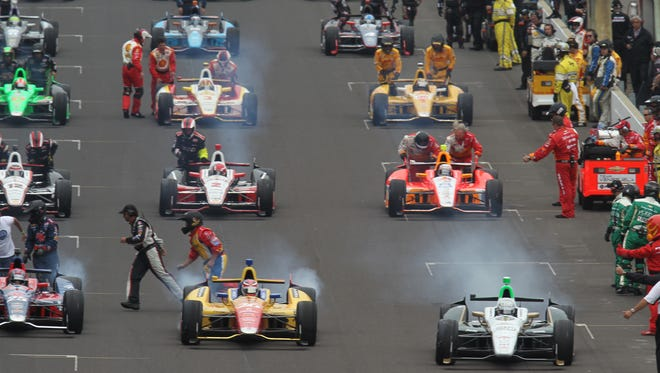 Team members run off the track after starting the engines for the field of 33 race cars for the 97th running of the Indianapolis 500 at the Indianapolis Motor Speedway on Sunday, May 26, 2013. Charlie Nye / The Star