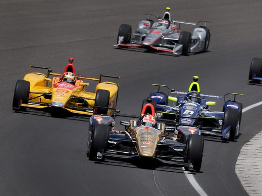 IndyCar driver James Hinchcliffe (5) leads the pack into turn one during the 100th running of the Indianapolis 500 Sunday, May 29, 2016, afternoon at the Indianapolis Motor Speedway.