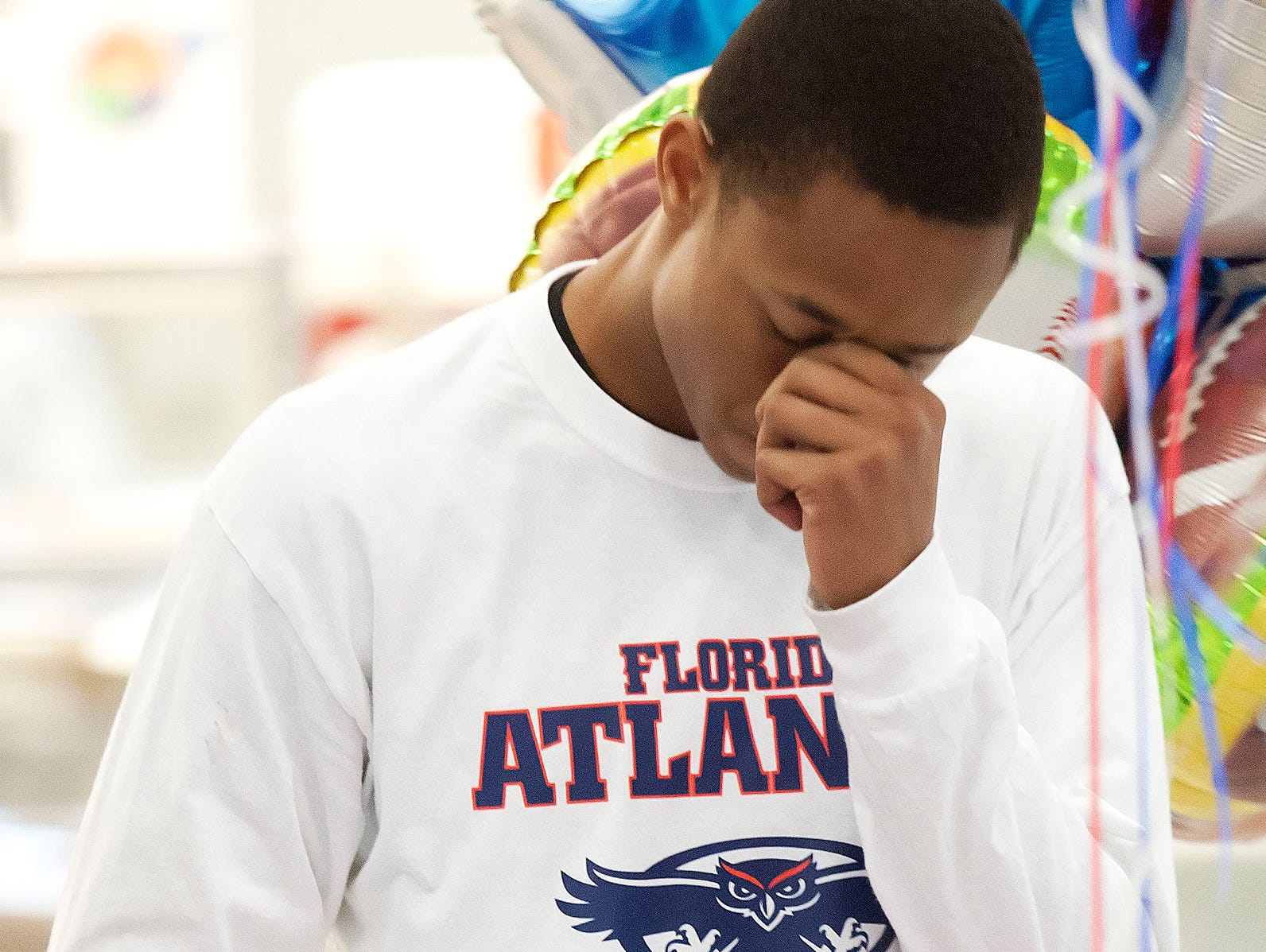 Fort Myers High School's James Brunson cries after speaking of his late father, James Brunson Sr., on Wednesday at Fort Myers High School. Brunson signed a National Letter of Intent to play football at Florida Atlantic University.