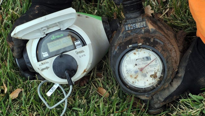 An RTS Water Solutions installation technician compares the new 'smart' meter (left) with the city's older meter in this December file photograph. The water meter replacement project began in July 2016 and is expected to be completed by early to mid summer this year.
