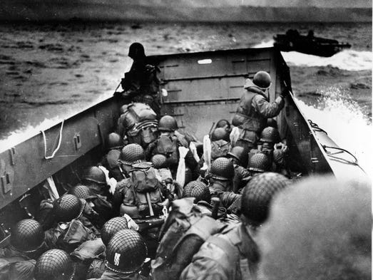 In this photo provided by the U.S. Coast Guard, a U.S. Coast Guard landing barge, tightly packed with helmeted soldiers, approaches the shore at Normandy, France, during initial Allied landing operations, June 6, 1944. These barges ride back and forth across the English Channel, bringing wave after wave of reinforcement troops to the Allied beachheads.