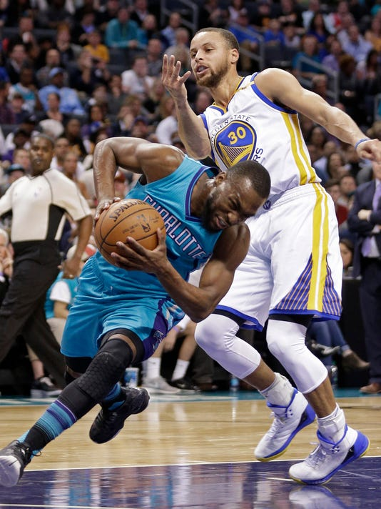 Charlotte Hornets' Kemba Walker, front, is fouled by Golden State Warriors' Stephen Curry in the first half of an NBA basketball game in Charlotte, N.C., Wednesday, Jan. 25, 2017. (AP Photo/Chuck Burton)
