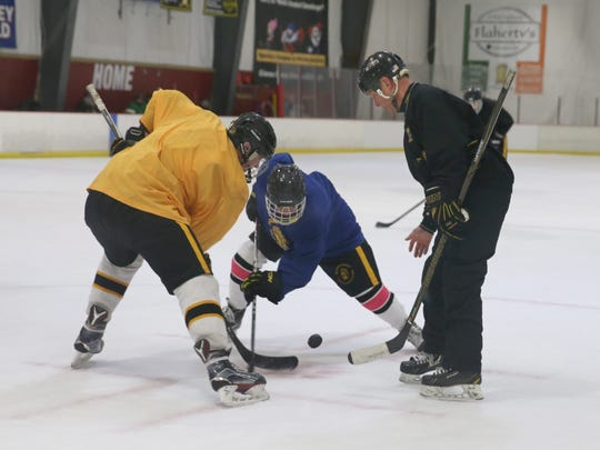 Head coach Al Vyverberg drops the puck for a face off as he leads his McQuaid hockey squad through practice at Village Sports in Fairport last week.  Vyverberg, 62, is retiring after 30 seasons as Section V's most successful high school coach.