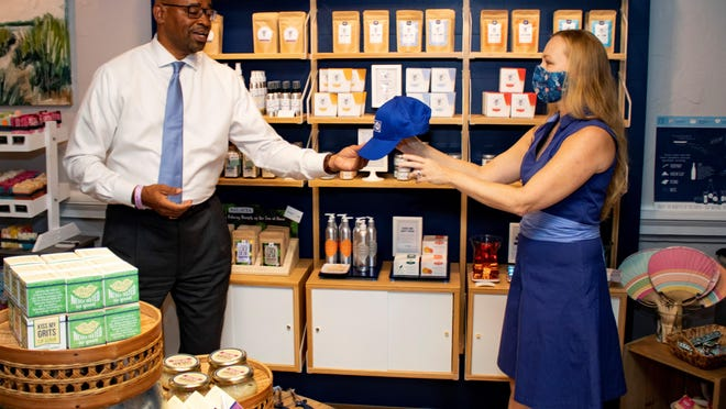 Cari Clark Phelps, (right) owner of Savannah-based Salacia Salt, receives a work hat from Terry Enoch as a thank you for the business' support for the local United Way.