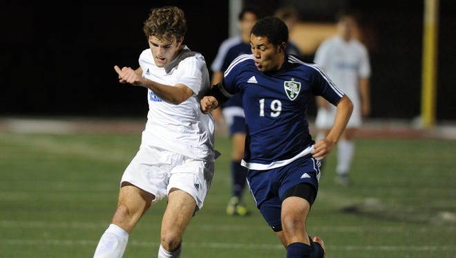 Sacred Heart's Larry Gibson, left, passes the ball as the Crusaders play against St. Patrick in the Class 1A/2A/3A South State championship match on Wednesday.